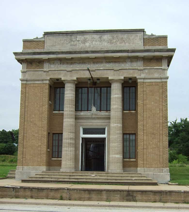"""Panel relief above The Ladora Savings Bank states: """"The Wealth of this community embodies the richness of her soil, the integrity, frugality and diligence of her people."""""""